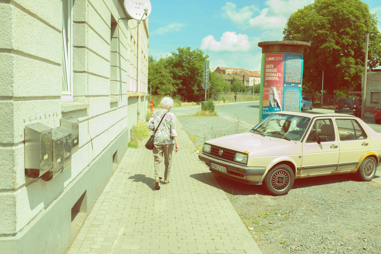 Die ältere Frau mit dem älteren Auto